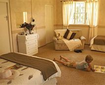 Large main bedroom with double bed, single bed and cot for small children.