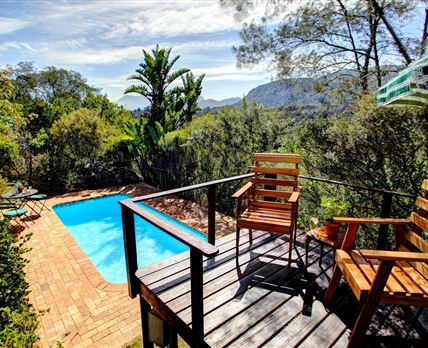 Sunny pool deck with patio overlooking the Outeniqua Mountains