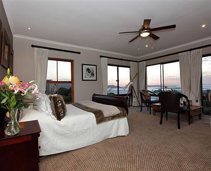 The room has with floor-to-ceiling windows offering stunning views, and a queen-size sleigh bed.