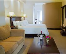"The Luxury King Suites are approximately 30m2 in size equipped with a King Size bed. The en-suite bathroom comes standard with a double vanity, separate bath and shower. Includes: Air-conditioning, King Size bed, Free Wi-Fi, 50"" DSTV, guest amenities, desk, tea and coffee making facilities, kettle, bar fridge and hairdryer."