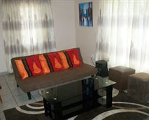 Lounge area. The seat converts into a bed. Coffee table, coffee table books and magazines, carpet, overhead lighting. An extra bed can be added her