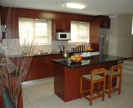 The well equipped kitchen with granite tops seen from the lounge area.