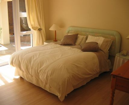 The spacious master bedroom has a comfortable king-size bed with cotton percale linen.