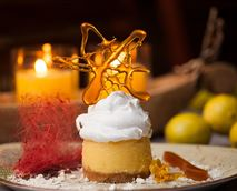Lemon and egg curd bake on biscuit crust and meringue topping, served with caramel bits and coconut shavings, and spun sugar. © Rooiberg Safaris