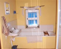 This quaint bathroom has a bath and shower, and lovely fresh towels supplied with soap and shampoo.
