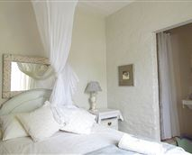 The perfect room for a romantic getaway.  Beautiful white linen and a mosquito net for those hot summer nights © Destination McGregor