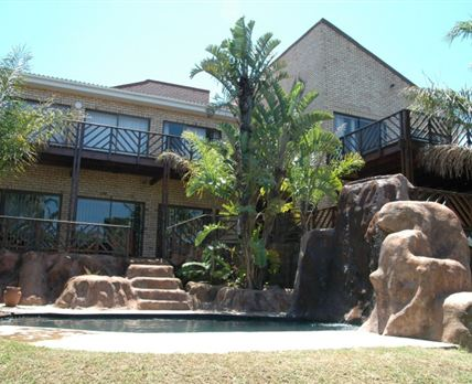 Pool/Jacuzzi with rock art and wooden deck
