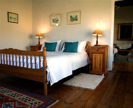 The Kammanassie Room is a double bedroom, beautifully decorated with antiques and double doors leading onto the wide veranda with farm views.