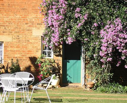 In spring and summer the bright mauve bougainvillea hangs over the entrance and often has a sun birds nesting in it.