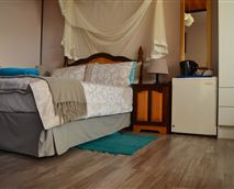 This room has a double and a single bed with an en suite shower, toilet,wash basin with mirror. There is a mini fridge, flat screen tv and tea& coffee making facilitiy available in the room.The room is upstairs and opens onto a sundowner deck.
