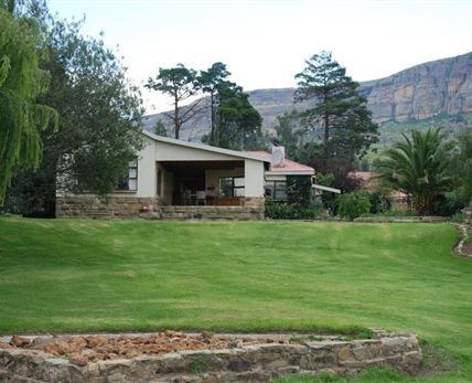 Rolling lawns and majestic mountain in the background are the setting for this stunning farm house.