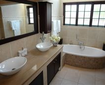 Bathroom with large shower, dressing room, and skylight over the bath.