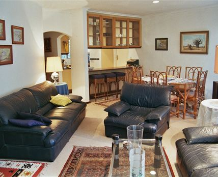 The living area is furnished with two three seater comfortable leather couches.