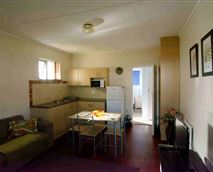 Open-plan lounge and kitchen in the self-catering one-bedroom unit