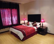 Vary spacious bedroom with wooden floors.