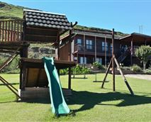 Landscaped garden with jungle gym and trampoline