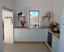 Fully-equipped kitchen with fridge, microwave, gas hob, and electric oven.