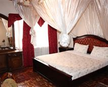 Spacious, king-size bed, TV, instant shower with bathtub, sitting area and a wall mirror with beautiful decorations.