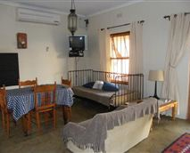 This is the living area in the cottage which includes a sitting area, dining area and kitchen. © Della Vigna Cottage