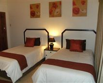 Comfortable en-suite room with two three-quarter beds.