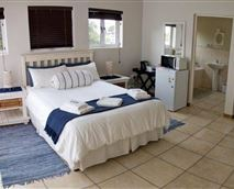 Guest room with double bed, bathroom, DSTV, microwave, bar fridge, coffee/tea facility