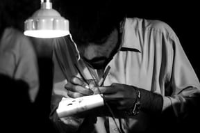 Man writing names on a grain of rice outside J.A.G