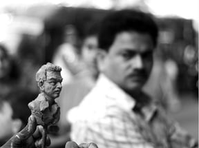 Man posing for sculptor outside J.A.G
